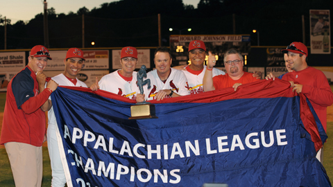 Members of the Cardinals coaching staff hoist the championship trophy.