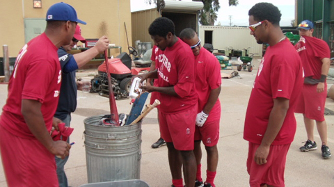 "Pitcher Ariel Pena adds lighter fluid to a pile of ""cursed"" equipment."