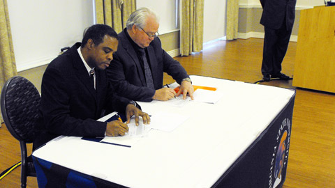 VSU President Keith Miller signs the agreement beside MiLB President Pat O'Conner.