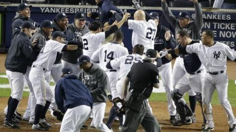 Raul Ibanez (27) leaps into home plate after a walkoff homer against the Orioles in Game Three of the ALDS.