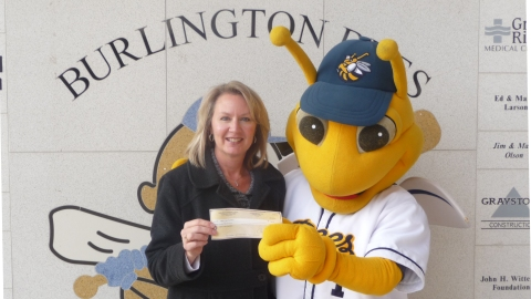 Bees' mascot Buzz presents the donation to regional volunteer Diane Roelfs.